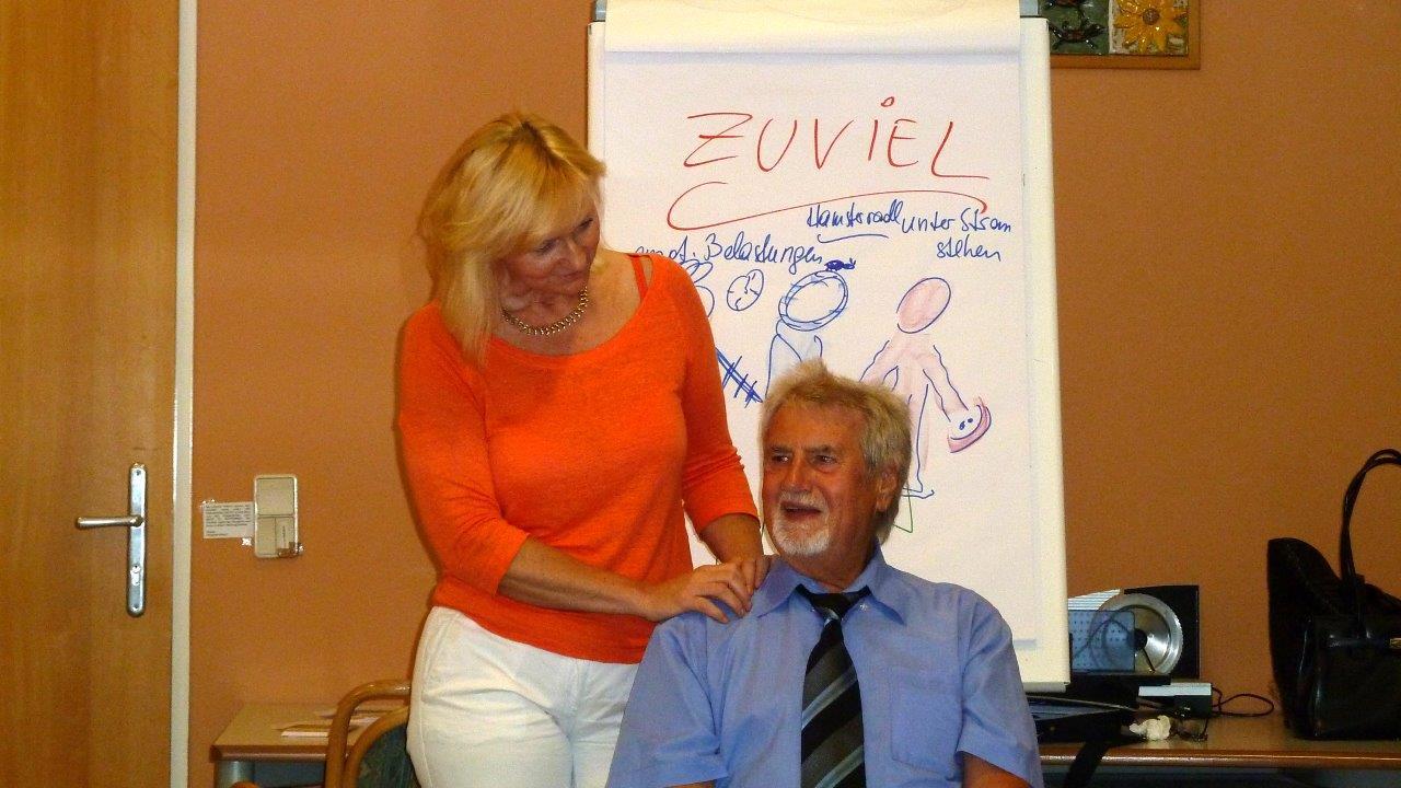 Blonde Frau mit orangen Top massiert einen bärtigen 65jährigen Mann mit blauem Hemd und Krawatte . Im Hintergrund steht eine Flipchart auf dem die Begriffe ZU VIEL steht.