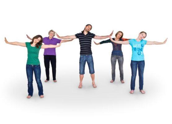 5 TeilnehmerInnen haben die Arme seitlich weggestreckt und dehnen den Nacken