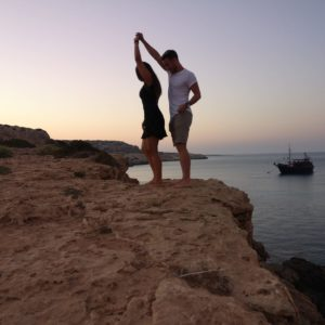 junges Pärchen tanzt im Sonnenuntergang auf einer Klippe. rechts davon liegt weiter unten das Meer