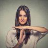 Frau mit langen braunen Haaren zeigt mit ihren Händen ein Stopp an